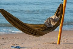 Rede na praia no por do sol com bokeh de incandescência do mar azul Rede verde com um chapéu e as sapatas, ardósias Fotografia de Stock