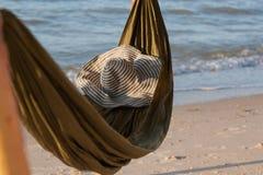 Rede na praia no por do sol com bokeh de incandescência do mar azul Rede verde com um chapéu e as sapatas, ardósias Imagens de Stock