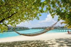Rede na praia tropical com os bungalows excedentes da água no recurso Fotografia de Stock