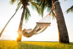Rede nas palmeiras tropicais que negligenciam as montanhas fotografia de stock royalty free