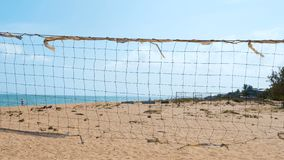 Rede rasgada velha do voleibol em um Sandy Beach filme