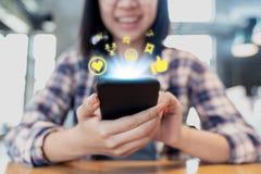 Rede social dos meios do smartphone ascendente próximo que compartilha e que comenta na comunidade online Telefone celular da ter foto de stock