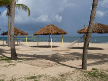 Rede, Tiki Huts, e rede do voleibol na praia Fotografia de Stock Royalty Free