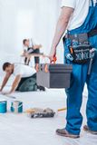 Specialist holding a toolbox. Redecorating specialist holding a large, iron toolbox in his left hand while his friends work royalty free stock photography