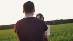 Redemoinho alegre dos amantes ao redor na natureza Abraço bonito e beijo dos pares que expressam o amor Luz do por do sol Mo lent filme