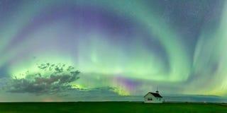Redemoinho de Aurora Borealis Northern Lights sobre a escola norte histórica da aterrissagem de Saskatchewan fotografia de stock