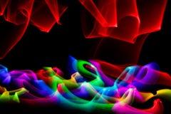 Redemoinho de luzes coloridas contra o fundo preto fotografia de stock royalty free