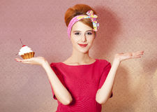 Reden Sie Redheadmädchen mit Kuchen am rosa Hintergrund an. Lizenzfreie Stockbilder