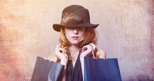 Reden Sie Rothaarigefrau im Hut mit der Feder an, die Einkaufstaschen hält Lizenzfreies Stockbild