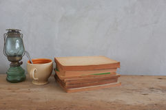 Reden Sie Weinlese Kaffeetasse, Kerosinlampen, alte Bücher auf Holz an Lizenzfreies Stockfoto