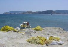 Redes amarelas da pesca em uma rocha branca com um pesca-barco, o mar e as montanhas na distância Ilha dos Milos em Grécia Foto de Stock