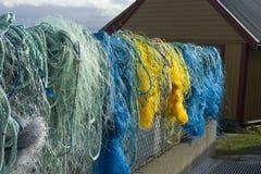 Redes coloridas dos peixes, cordas e o outro equipamento de pesca em Noruega Imagens de Stock