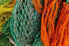 Redes de pesca alaranjadas, azuis, verdes e amarelas no cais fotografia de stock