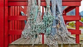 Redes de pesca azuis e suspensão verde no vermelho da cerca ou do patamar Imagens de Stock