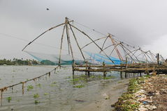 Redes de pesca chinas en la playa, la India Fotos de archivo libres de regalías