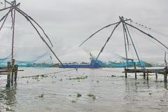 Redes de pesca chinas en la playa, la India Imagenes de archivo