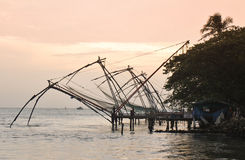 Redes de pesca chinas en la puesta del sol Imagen de archivo libre de regalías