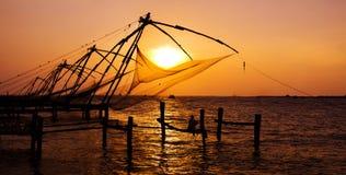 Redes de pesca de Cochin en la puesta del sol Fotos de archivo