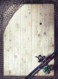 Redes de pesca e ainda-vida da vara de pesca no fundo de madeira Fotografia de Stock