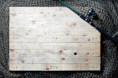 Redes de pesca e ainda-vida da vara de pesca no fundo de madeira Imagens de Stock Royalty Free