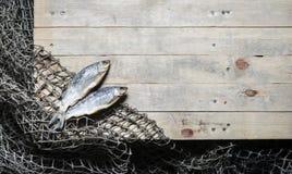 Redes de pesca e ainda-vida secada dos peixes no fundo de madeira Foto de Stock