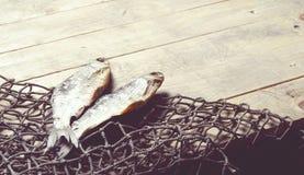 Redes de pesca e ainda-vida secada dos peixes no fundo de madeira Fotografia de Stock