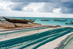 Redes de pesca grandes que mienten en la playa africana con los barcos cerca de la orilla foto de archivo