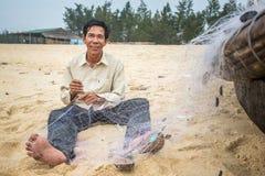 Redes de pesca no identificadas del repairin de los pescadores Fotos de archivo libres de regalías