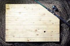 Redes de pesca y aún-vida de la caña de pescar en el fondo de madera Imagen de archivo libre de regalías