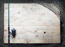 Redes de pesca y aún-vida de la caña de pescar en el fondo de madera Imagenes de archivo