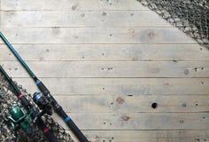 Redes de pesca y aún-vida de la caña de pescar en el fondo de madera Foto de archivo