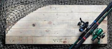 Redes de pesca y aún-vida de la caña de pescar en el fondo de madera Imágenes de archivo libres de regalías