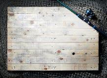 Redes de pesca y aún-vida de la caña de pescar en el fondo de madera Fotografía de archivo