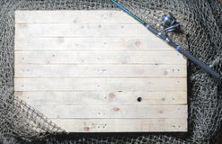 Redes de pesca y aún-vida de la caña de pescar en el fondo de madera Foto de archivo libre de regalías