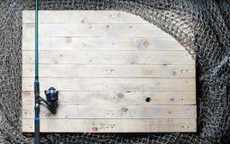 Redes de pesca y aún-vida de la caña de pescar en el fondo de madera Fotografía de archivo libre de regalías