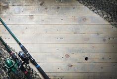 Redes de pesca y aún-vida de la caña de pescar en el fondo de madera Imagen de archivo