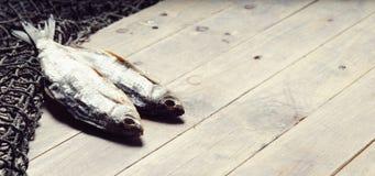 Redes de pesca y aún-vida secada de los pescados en el fondo de madera Fotografía de archivo