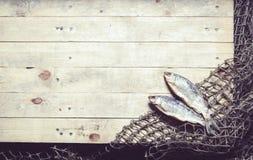 Redes de pesca y aún-vida secada de los pescados en el fondo de madera Fotos de archivo libres de regalías