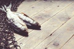 Redes de pesca y aún-vida secada de los pescados en el fondo de madera Foto de archivo