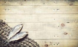 Redes de pesca y aún-vida secada de los pescados en el fondo de madera Imágenes de archivo libres de regalías