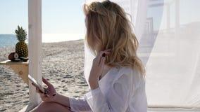 Redes sociales de visión, teléfono móvil el vacaciones de verano, islas tropicales, muchacha atractiva en casa de planta baja en  almacen de metraje de vídeo