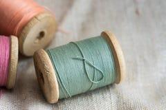 Redeten hölzerne Threadspulen VVintage auf Leinenstoff, Pastellfarben, Nahaufnahme, Bild an Stockbilder