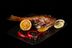 Redfish Grill. Sea bass grilled with lemon pepper and spicy on a black plate Royalty Free Stock Images