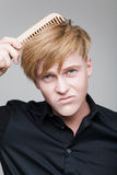 Redhair boy with wood comb. Royalty Free Stock Images