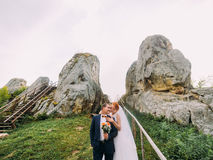 Redhair bride with happy handsome groom embracing in rocky Carpathian mountains. Tustan fortress Stock Photography