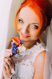 Redhair bride in a wedding dress with unusual appearance holds boutonniere and smiles Stock Images