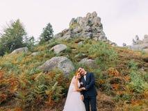 Redhair brud i den vita klänningen med den lyckliga stiliga brudgummen på bakgrund av steniga Carpathian berg Royaltyfria Foton
