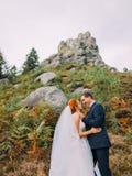 Redhair brud i en vit klänning med brudgumblick på de på bakgrund av steniga berg Royaltyfri Bild