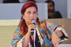 Redhair partecipant in Elegant colorful Jacket. Lady in multi colored elegant cloth speaking on microphone during Dubai Design District 2015 Stock Photos