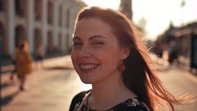 Redhair frais avec la femme de taches de rousseur au milieu de la ville Vent de soufflement Éclairage de coucher du soleil clips vidéos